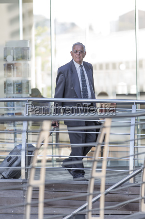 senior businessman leaving hotel with wheeled