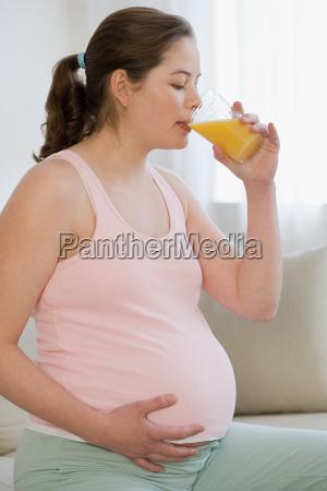 pregnant woman drinking orange juice