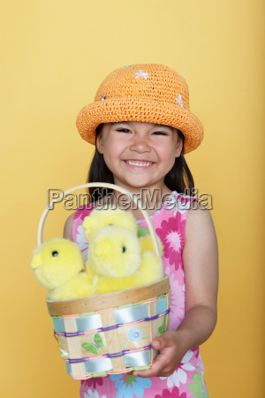girl holding a basket of chicks