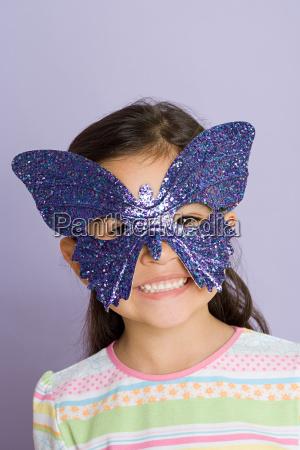 girl wearing a butterfly eye mask