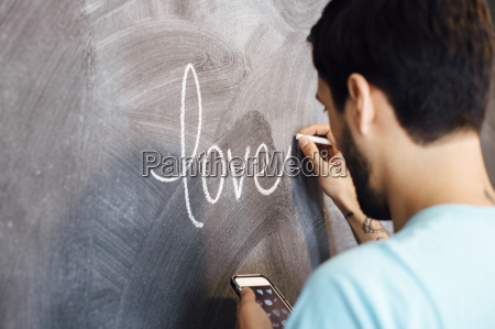 young man writing the word love