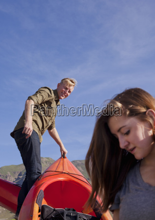 young couple preparing orange kayak