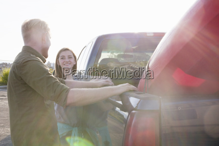 young couple leaning against pick up