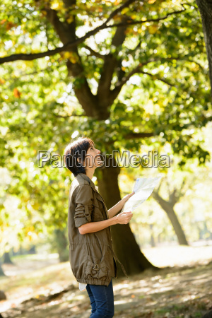 woman reading map in park