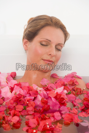 woman in a bath with petals