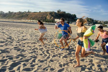 group of friends running on beach