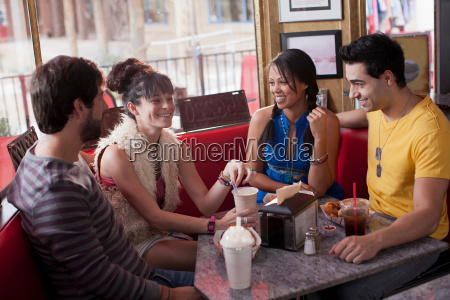 four friends sitting together in diner