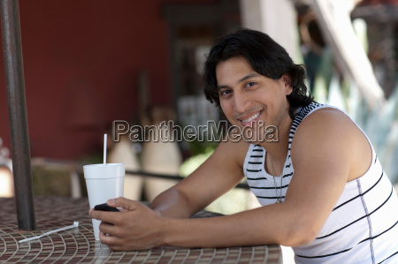 young man holding mobile phone in