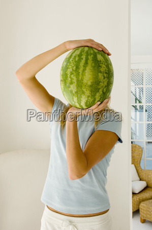 woman holding watermelon over face