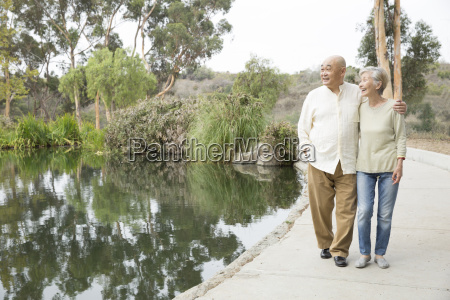 senior couple walking beside lake