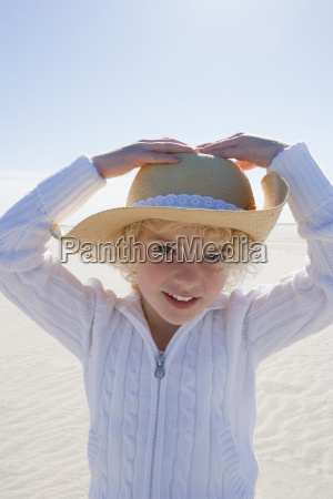girl wearing straw hat on beach