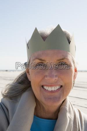 senior woman wearing paper crown