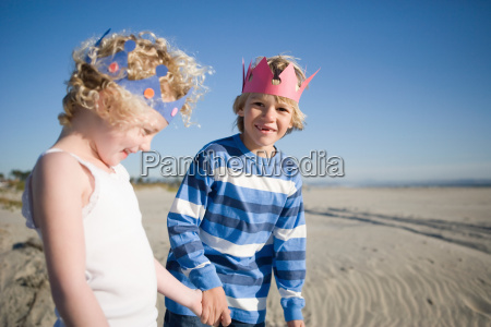 brother and sister wearing paper crowns