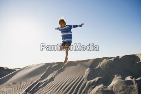 boy jumping on sand dune
