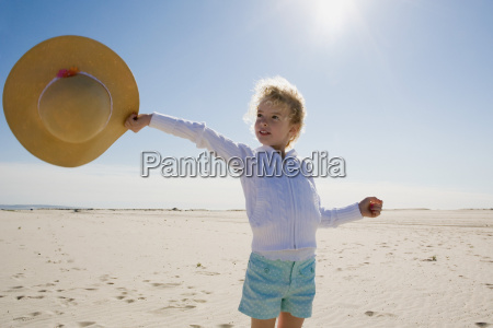 girl holding out straw hat on