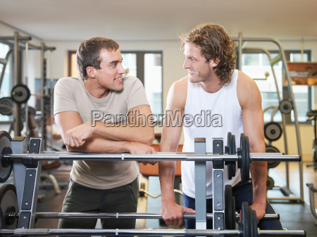 two men standing at exercising equipment
