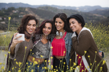 four adult sisters posing for smartphone