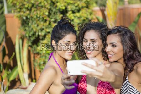three adult sisters wearing bikini tops