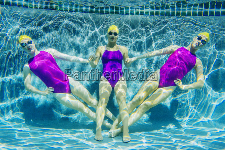 three female swimmers underwater holding hands