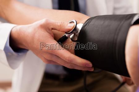 mittlere erwachsene arzt mit stethoskop und