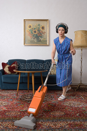 woman wearing headphones and vacuuming