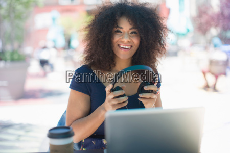 young woman holding headphones at sidewalk
