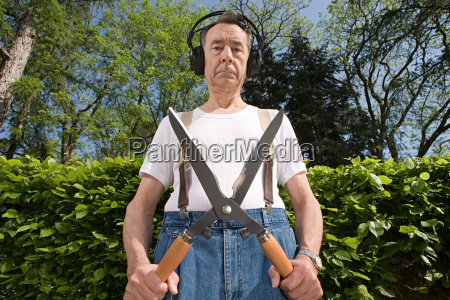 man wearing headphones and holding gardening