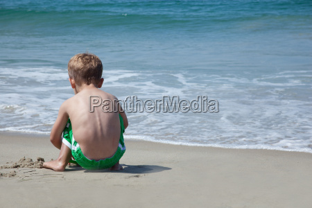 male toddler playing on beach