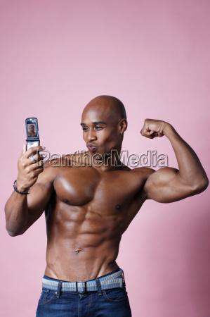 mann plext seine muskeln fuer kamera