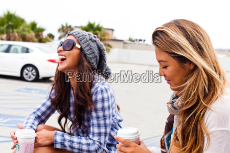 female friends sitting in car lot