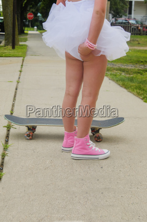 young girl standing next to skateboard