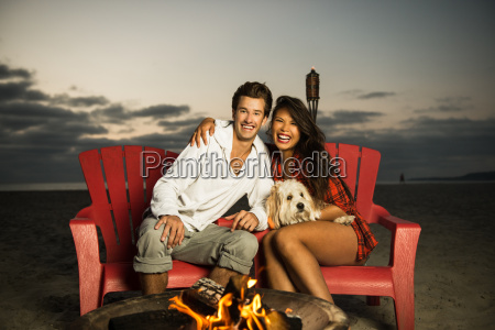 young couple sitting by campfire on