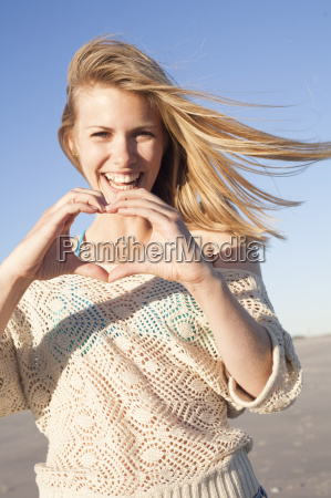 smiling woman making heart sign with