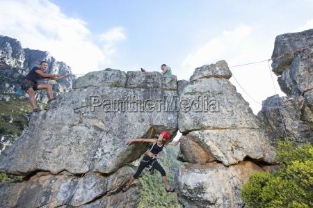 three rock climbers climbing up rock