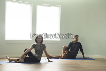 mature couple sitting on yoga mat