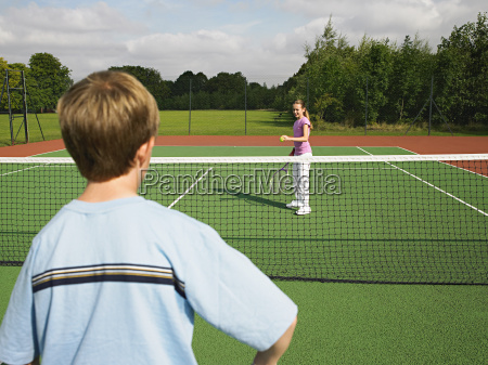 boy and girl playing tennis