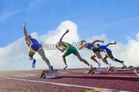 four female athletes on athletics track