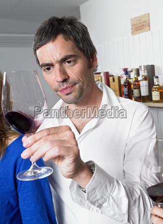 man examining glass of red wine