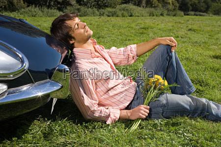 man relaxing by car in field