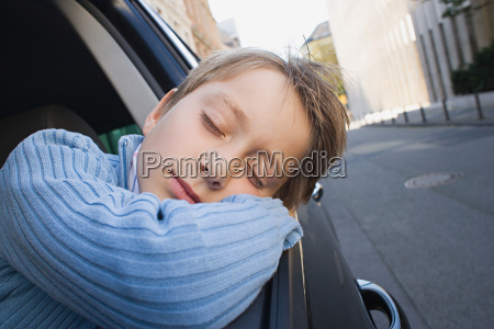 boy sleeping on car window