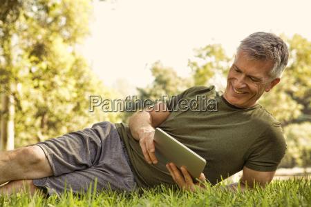 mature man looking at digital tablet