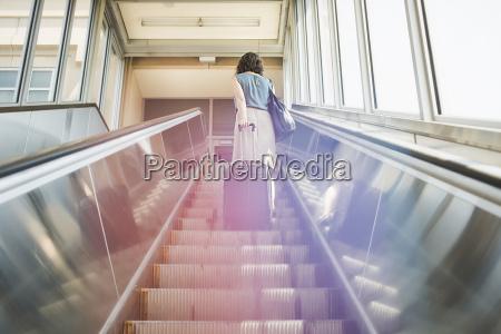 mid adult woman using escalator holding