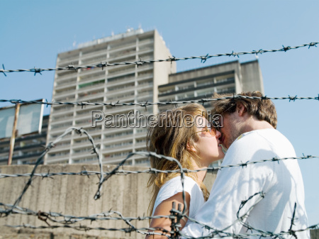 young couple kissing in urban setting