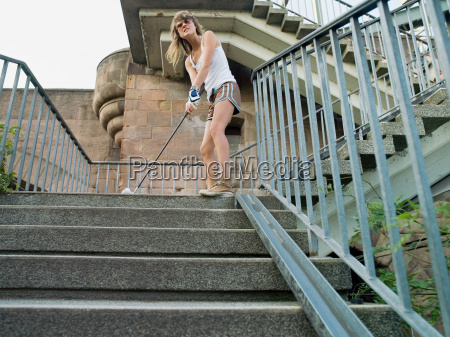 woman playing golf on steps
