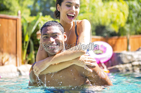 mid adult man carrying young woman