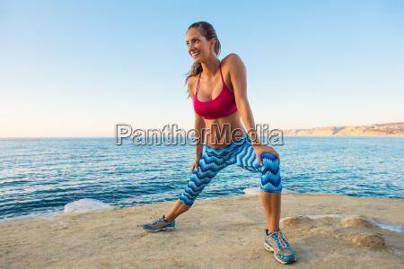 young woman doing stretches on beach