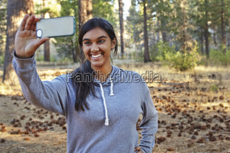 young woman in forest taking smartphone