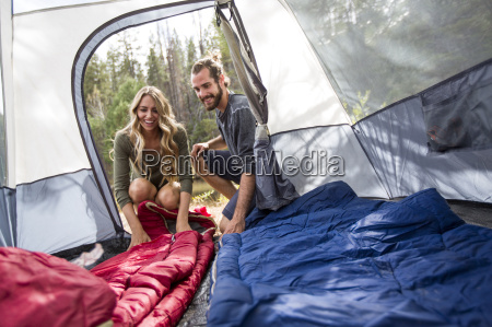 happy young couple looking into tent