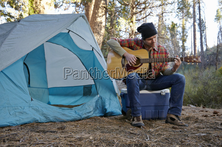 young male camper playing guitar in
