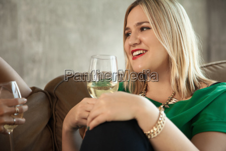 two female friends sitting on sofa
